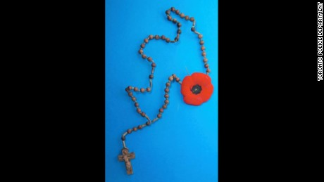 A rosary with a Remembrance Day poppy hung from a nail on the wall of mysterious Toronto tunnel.