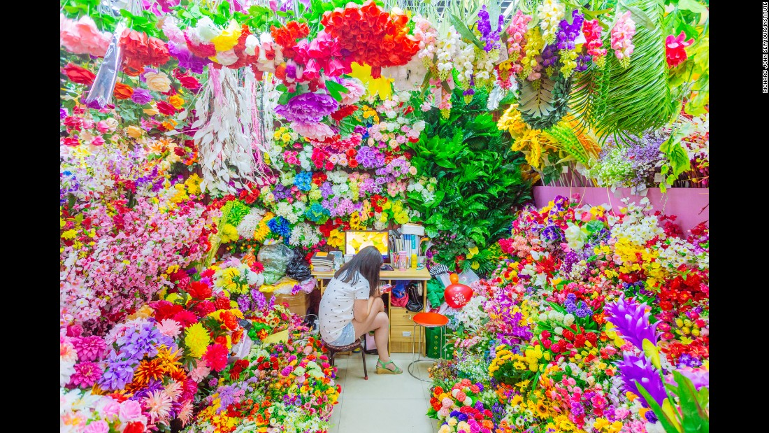 A seller sits among artificial flowers in one of the booths at Commodity City.