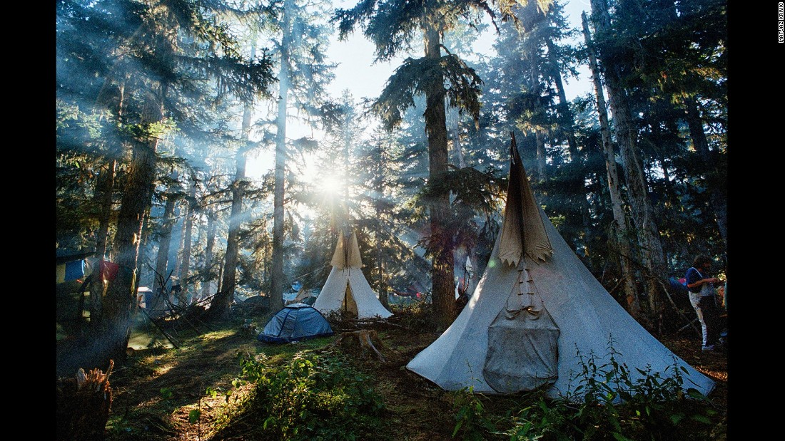 Light rays power through colossal trees, illuminating tents and tepees. According to Krivic, the exact locations of some of the Rainbow Gatherings are revealed through hand-drawn maps and presented to those who have attended a gathering in the past.