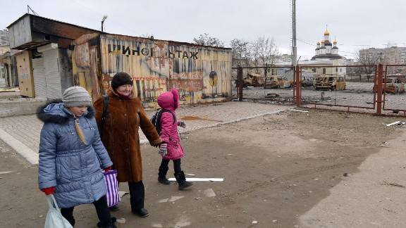 An elderly woman walks with young girls past cars burned after shelling near a church in the southeastern Ukrainian city of Mariupol, Donetsk region, on February 25, 2015. Despite the nominal truce in force, the key industrial hub has become the latest hotspot in the conflict in east Ukraine, stoking fears that pro-Russian rebel forces could be gearing up to try to seize the city. AFP PHOTO / GENYA SAVILOVGENYA SAVILOV/AFP/Getty Images