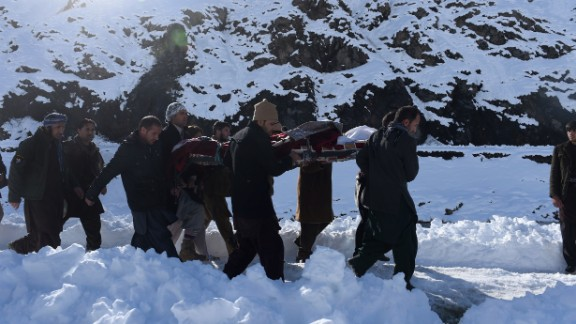 Men carry the body of an avalanche victim after funeral prayers in Khench, Afghanistan, on Thursday, February 26.