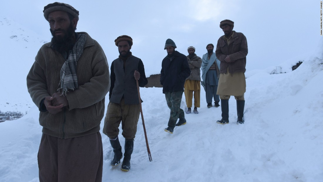 Men make their way down a slope after searching for victims in Bazarak district on Wednesday, February 25.