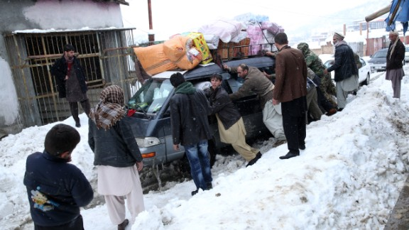 People push a car stuck near an avalanche site in Panjshir province February 25.