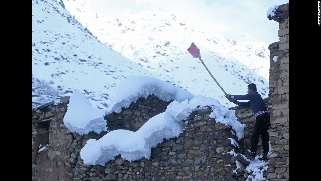 A teenager cleans off snow from the roof of his house in Panjshir province February 25.