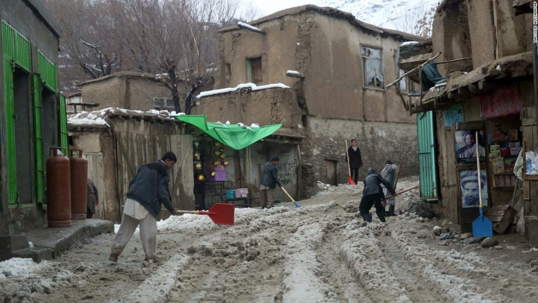People clean snow from a road in Panjshir province February 25.