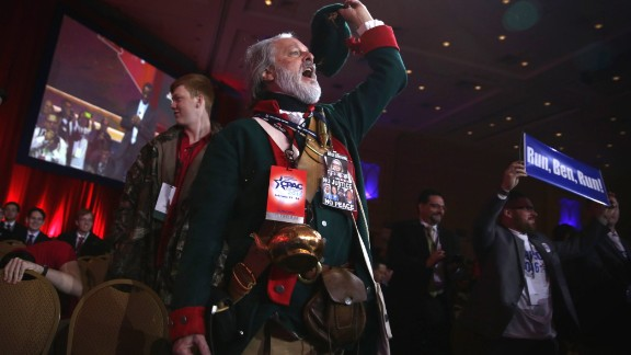 William Temple of the Golden Isles Tea Party in Georgia, dressed as Button Gwinnett, the second signer on the United States Declaration of Independence, cheers as Ben Carson speaks.