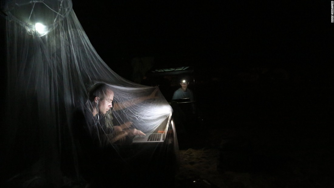 CNN photographer Brice Laine works under a mosquito net in a makeshift edit suite during Exercise Flintlock.