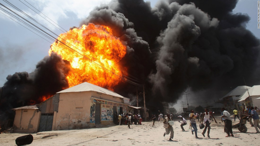 People run from an explosion at a petrol station and storage facility near the Bakara open-air market in Mogadishu, Somalia, on Monday, February 23.