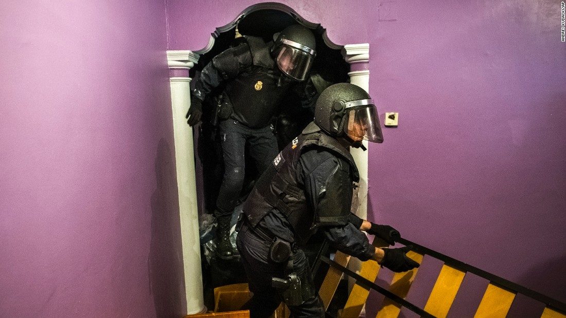 Police force their way into Emilia Montoya Vazquez's apartment after they broke down the main door to evict her and her family in Madrid on Wednesday, February 25.