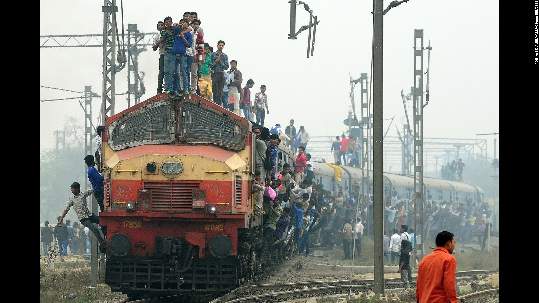 Indian passengers stand on a train as it departs from a station on the outskirts of New Delhi on Wednesday, February 25.