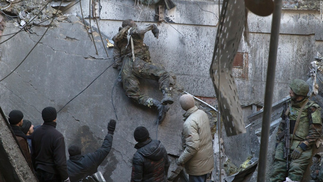 The body of a Ukrainian serviceman is removed from the rubble of the airport building outside Donetsk, Ukraine, on Wednesday, February 25, after a battle over the airport.