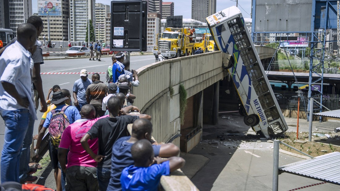 Onlookers gather on Queen Elizabeth Bridge in Johannesburg to look at a public bus that drove over the side on Wednesday, February 25, 2015.