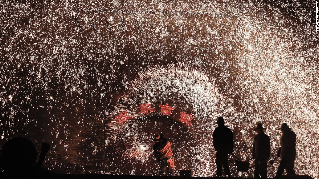 Chinese blacksmiths staff a furnace as molten metal is thrown against a cold stone wall to create sparks on Monday, February 23.