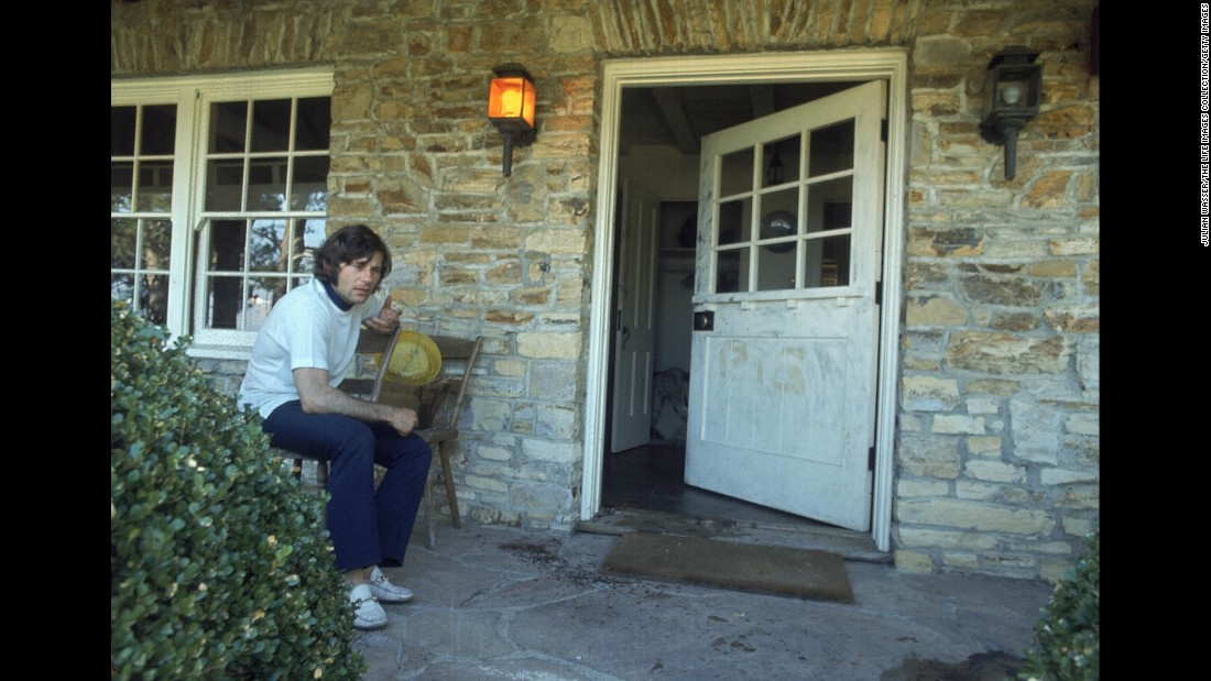 Polanski sits on the bloodied porch of his home after the bodies of his wife, Tate, and her friends were found inside in August 1969. Tate was one of five people murdered ritualistically by Charles Manson cult followers.