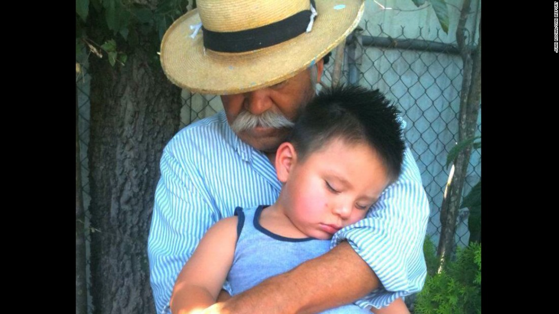 "Herminio holds his grandson in 2011. ""My father has always worked with his hands and this picture captures the roughness and contour of his hands as well as the sweet innocence of my son."""