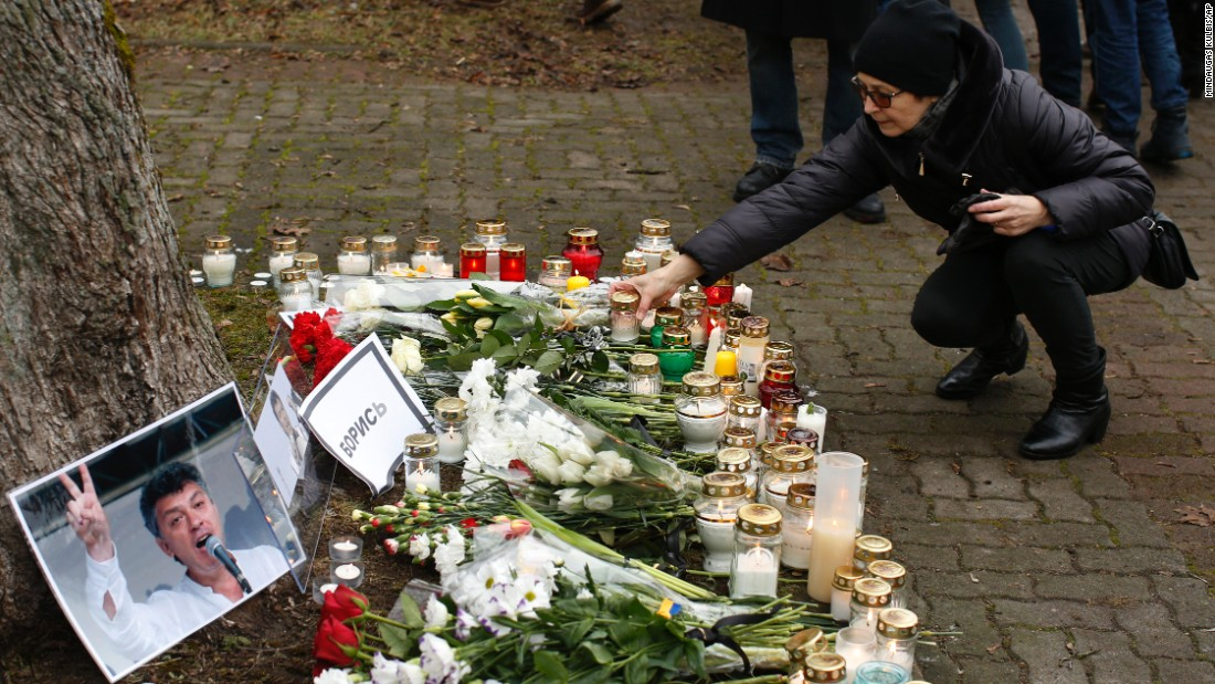 A woman places a candle at a makeshift memorial in front of the Russian Embassy in Vilnius, Lithuania, on March 1.