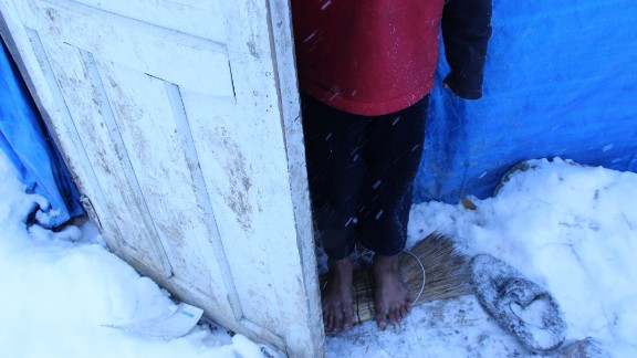 Seven-year-old Khalil stands barefoot on broom bristles in the snow at the entrance of his family