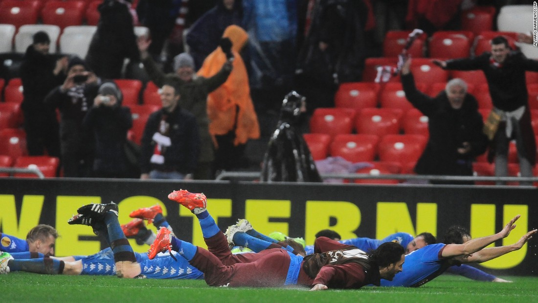 After a 3-2 victory over Athletic Bilbao, members of the Torino soccer club celebrate by sliding on the grass Thursday, February 26, in Bilbao, Spain. The victory pushed the Italian club into the Europa League's round of 16.