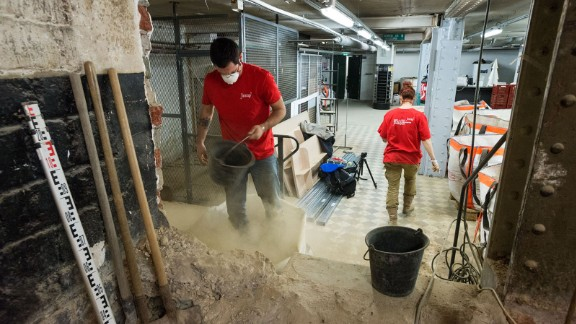 A team of archeologists sifts through dirt to unearth centuries-old skeletons under a Paris supermarket.