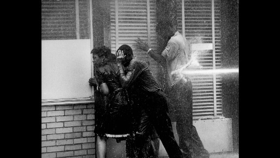 Demonstrators in Birmingham, Alabama, huddle in a doorway to seek shelter as authorities try to disperse them with water hoses in 1963.