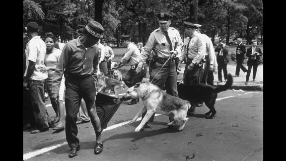 """A man looks calmly over his shoulder as a police dog in Birmingham rips his trouser leg in 1963. """"The figure in the photo is a perfect symbol of nonviolence,"""" Kasher said. """"You know, the man is standing there, taking it, not fighting back, amid this incredible rush of hatred and violence and as another dog is charging right at Moore's -- at the viewer's -- face."""""""