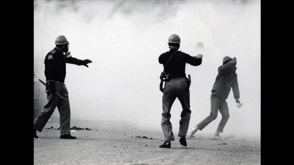 """Alabama state troopers wear gas masks as tear gas is fired on marchers in 1965. Fifty years ago, about 600 people began a 50-mile march from Selma, Alabama, to the state capital of Montgomery so that they could protest discriminatory practices that prevented black people from voting. But as the marchers descended to the foot of the Edmund Pettus Bridge, state troopers used brutal force and tear gas to push them back. It is now known as """"Bloody Sunday."""""""
