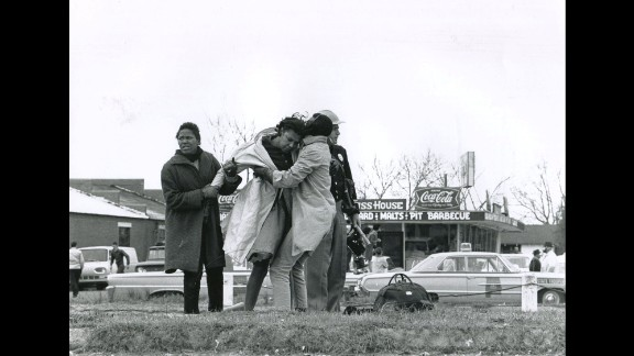 """Activist Amelia Boynton is helped to her feet after being knocked unconscious by a state trooper. """"The quality, the depth, the sense of reality that (photographer Charlie Moore) brings to the work is unparalleled,"""" said Steven Kasher, whose gallery is showing the Selma images of Moore and other essential witnesses of the civil rights era."""