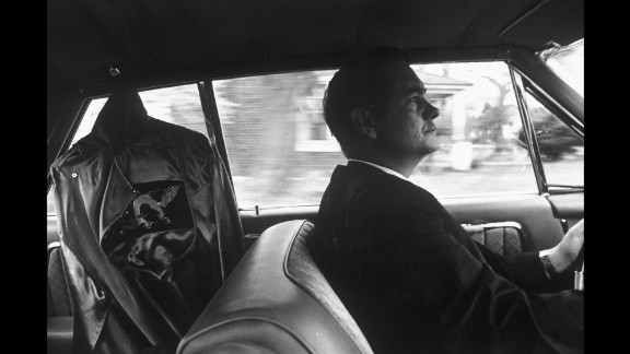 """A Ku Klux Klan """"grand dragon"""" drives to a rally in North Carolina with a Klan robe hanging in the back seat of his car in the mid-1960s."""