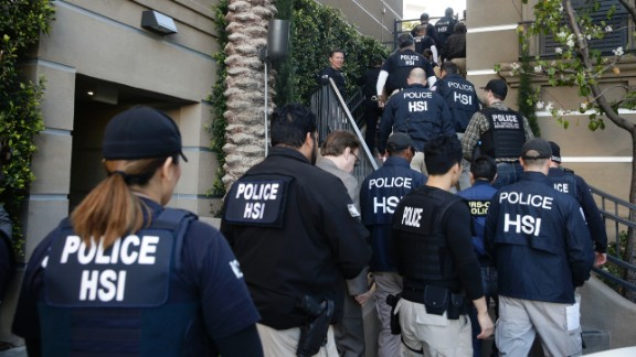 """Federal agents enter an upscale apartment complex on Tuesday, March 3, in Irvine, California. More than three dozen """"maternity hotels"""" were raided in Southern California, where foreign women give birth, allegedly for the sole purpose of having a U.S.-citizen baby, authorities said."""