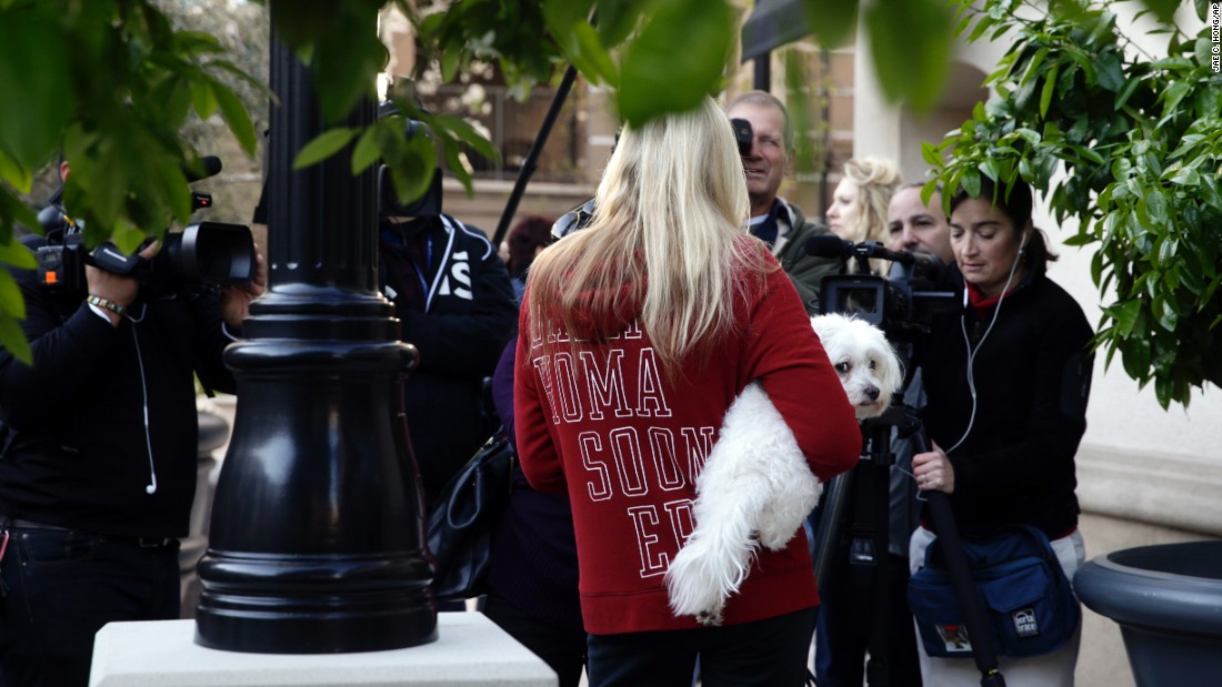 A resident holds her dog while talking to reporters at an apartment complex. Authorities are looking for evidence of bringing in and harboring of undocumented visitors; conspiracy, fraud and misuse of visas and permits; tax evasion and false tax returns; and willful failure to file report of foreign bank and financial accounts, court papers said.