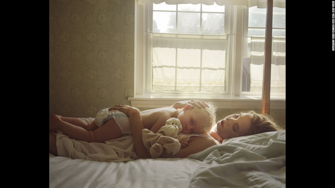 "Photographer Jessica Todd Harper lies on a bed with her son Marshall in 2009. It is one of the photos in her book ""The Home Stage."""