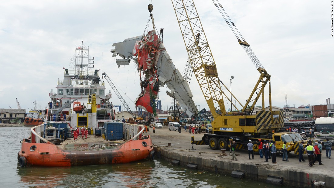 Crews remove the fuselage of AirAsia Flight QZ8501 from a vessel at the Tanjung Priok Port in Jakarta, Indonesia, on Monday, March 2. AirAsia Flight QZ8501 was en route from Surabaya, Indonesia, to Singapore when it lost contact with air traffic control on December 28. There were 162 people on board.