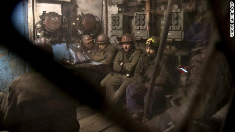 Ukrainian coal miners wait in a room before going underground to help search for the bodies.