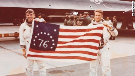 Airmen Al Joersz, left, and George Morgan hold a bicentennial American flag after breaking the world aviation speed record in 1976.