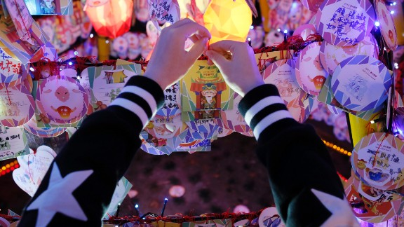 A visitor attaches a new year wish to a row of lanterns at the start of the Lantern Festival marking the end of Chinese Lunar New Year celebrations in Taipei, Taiwan, on Thursday, March 5.