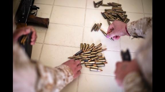 Female Peshmerga load rifle magazines.