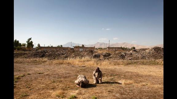 Two female Peshmerga pray during the afternoon.