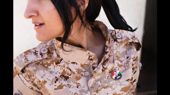 A female Peshmerga wears a badge depicting Iraqi President Jalal Talabani, who is Kurdish.