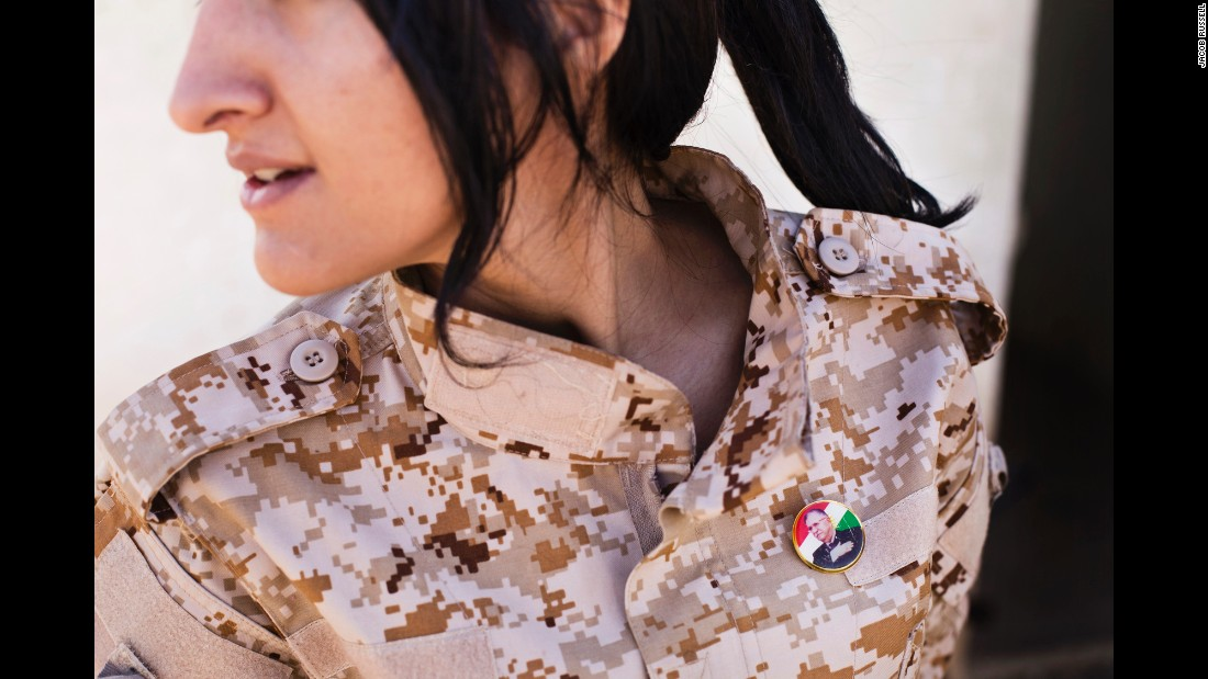 A female Peshmerga wears a badge depicting Iraqi President Jalal Talabani, who is Kurdish.