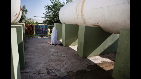 A female Peshmerga prays near water tanks at the base in Sulaymaniyah.