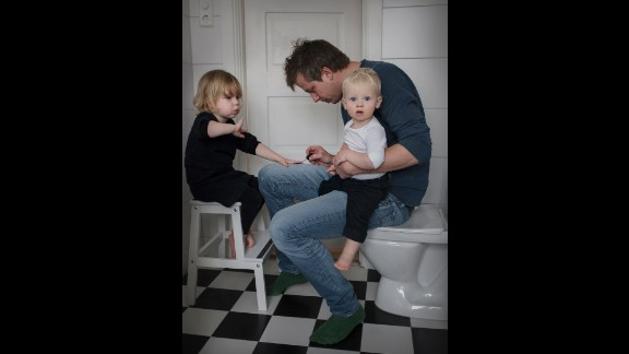 Martin Gagner, 35, holds Valdemar, 1, as he paints the nails of 4-year-old Matilda.