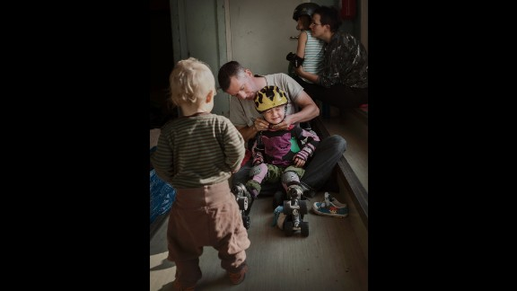 """Anton Cervin, 40, puts a helmet on Marit, 4, while 1-year-old Pia watches. """"I think more about gender equality now that I have two little girls,"""" he told Bavman."""