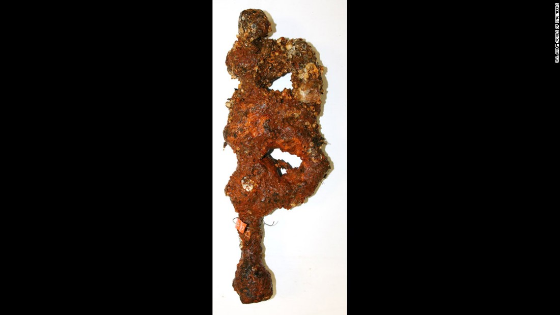 "One of the two leg irons recovered from the CSS Georgia site. ""Part of the iron is solid; some has eroded completely,"" said Jim Jobling of Texas A&M. Scientists will remove encrusted material and inject epoxy into the areas of deterioration. An exact replica will be made. Then the epoxy will be removed from the original item."