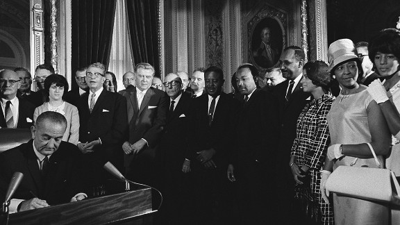 President Lyndon B. Johnson signs the Voting Rights Act in August 1965 as the Rev. Martin Luther King Jr. looks on. The act reshaped the South and eventually helped lead to the election of President Obama.