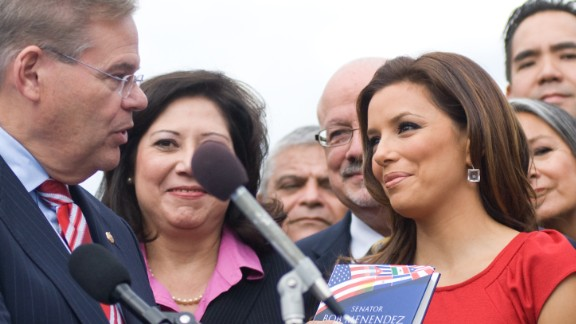 Senator Robert Menendez gives actress and activist Eva Longoria a copy of his book 'Growing American Roots' during a National Museum of the American Latino Commission press conference at the House Triangle on October 13, 2009 in Washington, D.C.