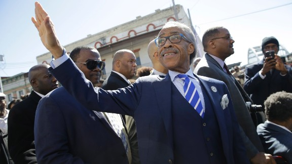 The Rev. Al Sharpton waves to supporters as he arrives.