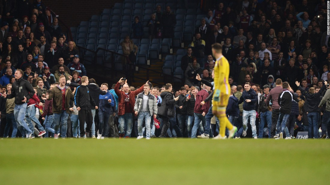 Villa fans flooded on to the pitch before the match was over. Supporters who remained in the stands initially booed those who entered the playing area.