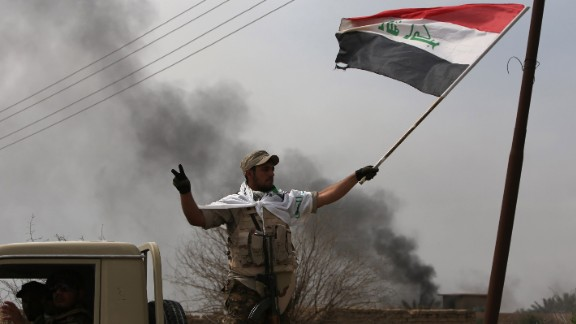 """Smoke billows in the background as a member of the Iraqi paramilitary Popular Mobilisation units flashes the """"V"""" for victory sign after regaining control of the village of Albu Ajil, near the city of Tikrit, from jihadists of the Islamic State (IS) group, on March 9, 2015. Some 30,000 Iraqi soldiers, police and the increasingly influential paramilitary Popular Mobilisation units, which are dominated by Shiite militias, have been involved in a week-old operation to recapture Tikrit, one of the jihadists' main hubs since they overran large parts of Iraq nine months ago.  AFP PHOTO / AHMAD AL-RUBAYE        (Photo credit should read AHMAD AL-RUBAYE/AFP/Getty Images)"""