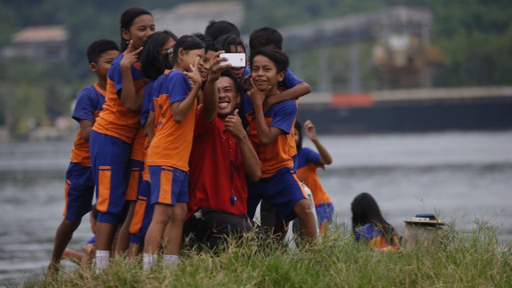 A teacher and students take a photo Thursday, March 5, at the Wijaya Pura port in Cilacap, Indonesia.