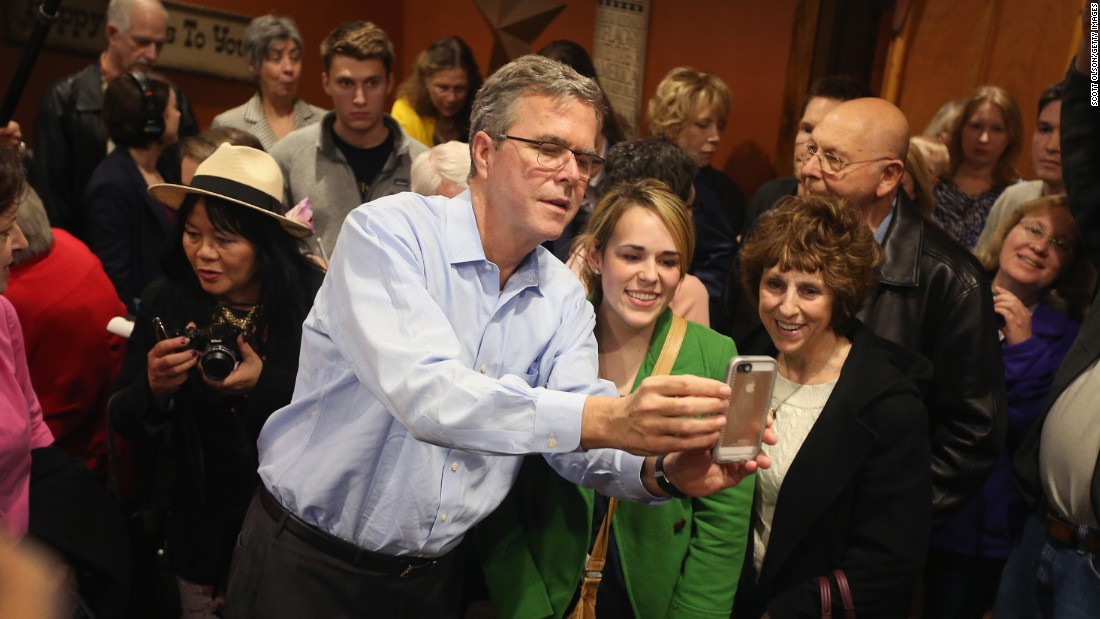 Former Florida Gov. Jeb Bush takes a selfie with Iowa residents after speaking at a restaurant in Cedar Rapids, Iowa, on Saturday. March 7.